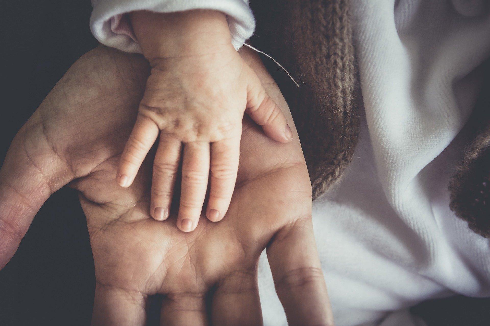 Pienen lapsen käsi aikuisen käden päällä